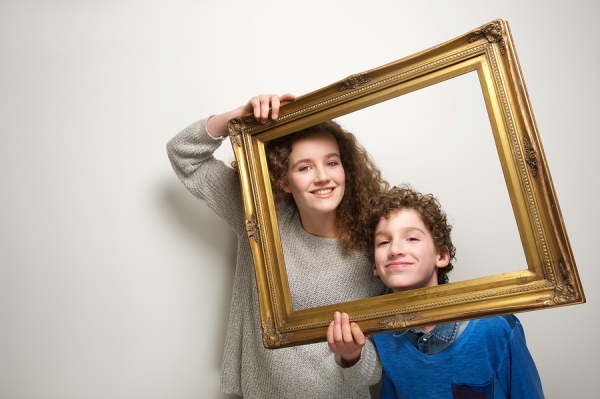 Portrait of a happy brother and sister holding picture frame