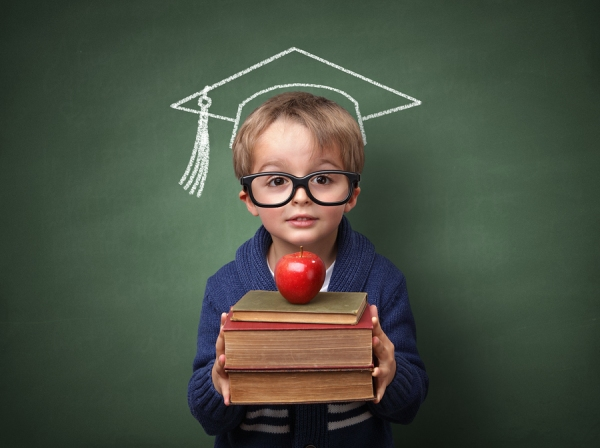 Child holding stack of books with mortar board chalk drawing on
