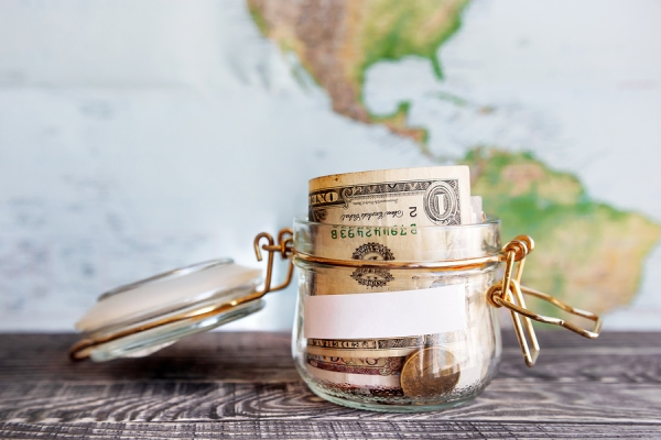 Collecting money for travel. Glass tin as moneybox with cash savings (banknotes and coins) on wooden table and map as background. White empty paper for text.