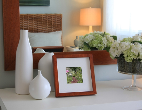 Picture frame and flowers on a dresser in a contemporary bedroom